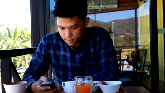 Young Boy using smart phone restaurant video