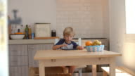 Young boy using tablet computer in kitchen, from doorway video