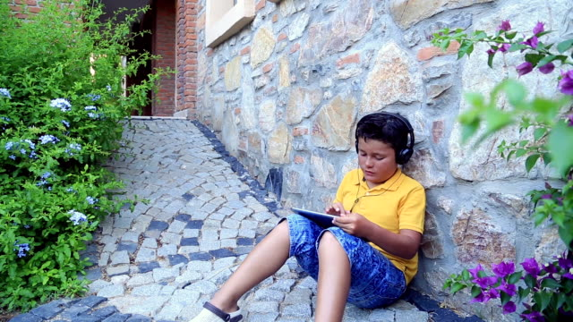 Young boy with  earphone using digital tablet video