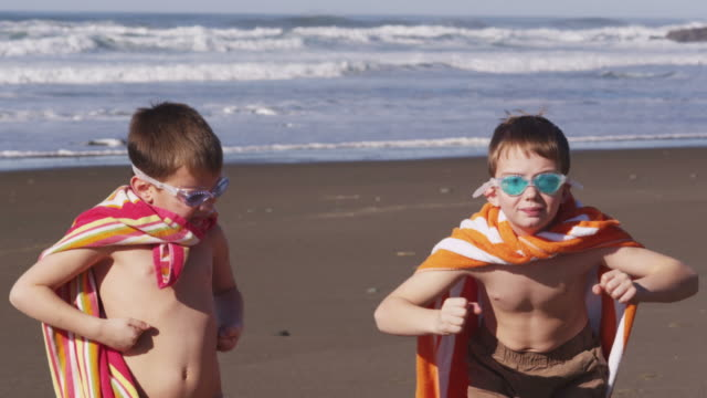 Young boys at beach flexing muscles with superhero costume video