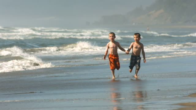 Young boys run on beach, slow motion video