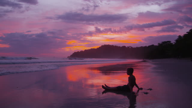 Young boys sitting on beach at sunset video