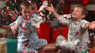 Young boys throw Christmas wrapping paper, slow motion video