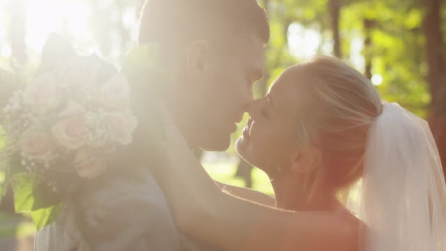 Young bride and groom are kissing in a sunny park. video