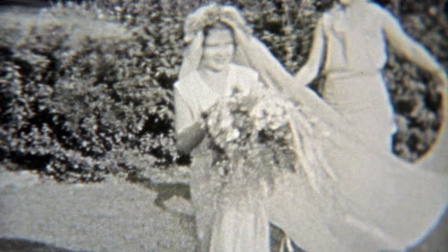 1937: Young bride tries on her dress while her servant helps. video