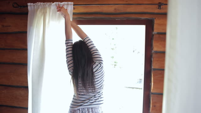 Young brown woman waking up from bed, pulling the curtain and stretching her arms. video