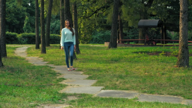 Young brunette girl is on a path in the park video
