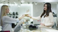 Young brunette girl is providing a credit card to the cashier at the cash desk in a department store. video