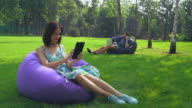 Young brunette girl is sitting in a chair in the park and swipe pages on your tablet video
