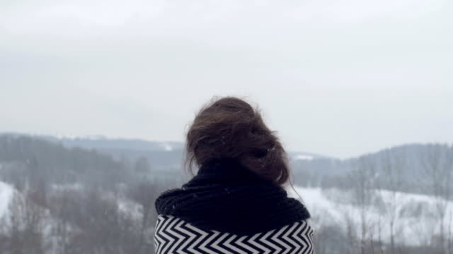 Young brunette girl looking at winter mountains, rear view. video