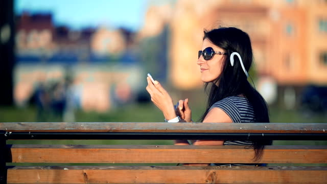 Young brunette straight hair woman in the park listening to music with headphones and smartphone video