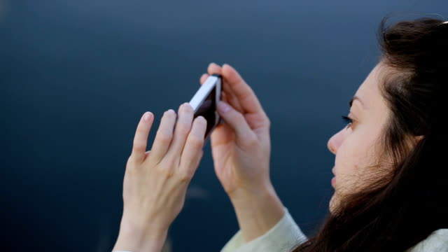 Young brunette woman doing photo using phone on nature video
