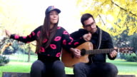 Young brunette woman singing while handsome man playing guitar video