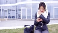 Young brunette woman sits outside with her phone video