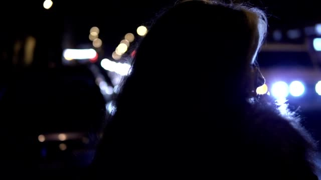 Young brunette woman stands on the street at night. City traffic at the background video