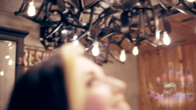 Young brunette woman touches the decorated lamps and turns to camera smiling video