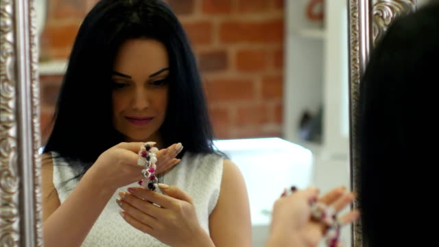 Young brunette woman trying handmade bracelet in front of mirror in the jewelry store video