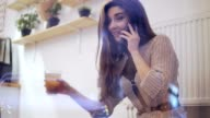 Young brunette woman viewed through window talking on the phone, smiling and drinking tea video