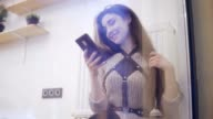 Young brunette woman viewed through window using her smartphone, chating and smiling video