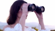 Young brunette woman watching with binoculars. video