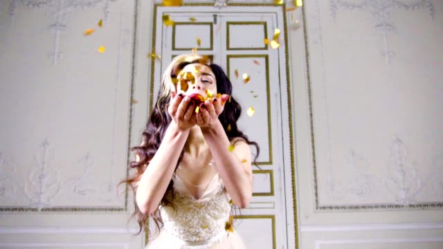Young brunette woman with red lips blows gold confetti video