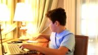 Young burunette boy using laptop video