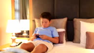 Young burunette child with smart phone in bedroom video
