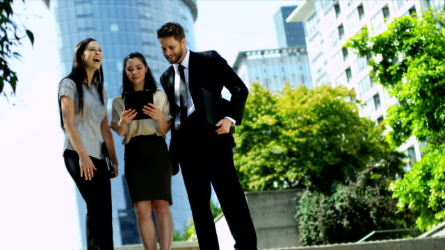 Young business colleagues using wireless tablet hot spot video