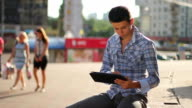 Young business man reading tablet pc computer on city square video
