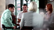 Young business people having fun in a cafe. video