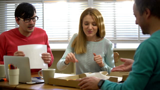 Young business team taking a break from work and eating pizza. Slow motion. video
