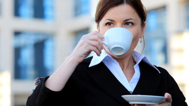Young business woman drinking coffee. video