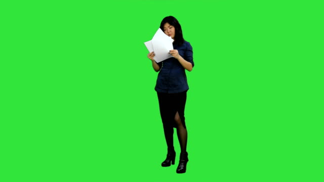 Young business woman holding documents, reading papers on a Green Screen, Chroma Key video