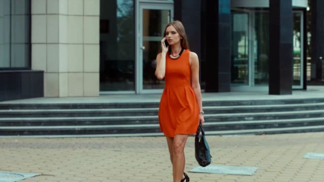 Young business woman in red dress talking on the phone on the street, urban background video