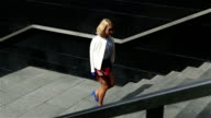 young business woman in short blue trunks up the stairs video