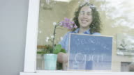 Young business woman opening a small business holding a 'We Are Open' sign video