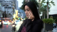 Young business woman talking with mobile phone with busy traffic as background. video