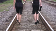 Young business women walking out on high hills. Railway path. video