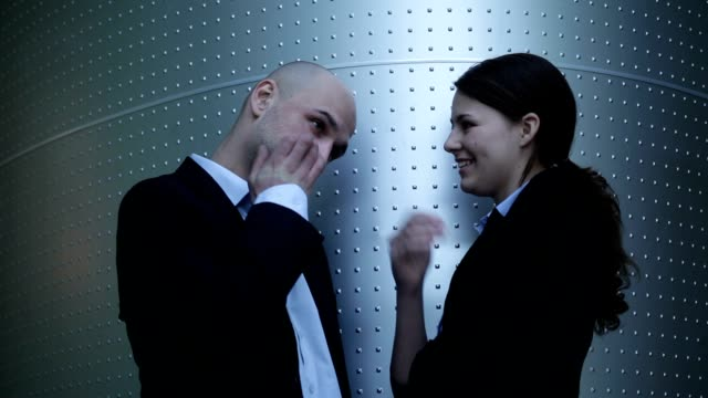 Young businessman and businesswoman flirting video