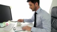Young businessman drinking coffee while working at the office video