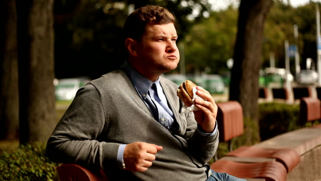 young businessman eating a hamburger video