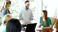 Young businessman explaining something to creative team in office board room video