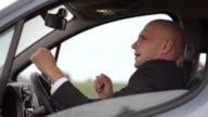 Young businessman has fun in the traffic jam. video