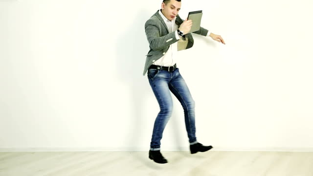 A young businessman holds a tablet in his hands and dances. video