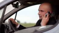 Young businessman in car talking on the phone, traffic jam. video