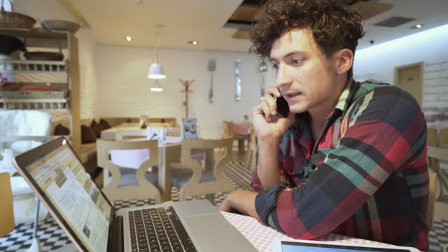 Young businessman on the mobile phone in a cafe. video