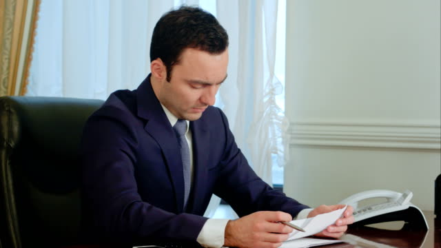 Young businessman reading paperwork at desk in office and smiling video