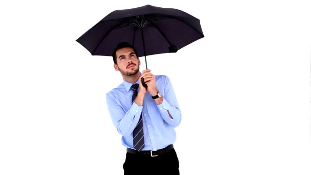 Young businessman sheltering with umbrella and putting it down video