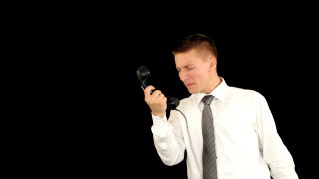 Young businessman shouting on the phone, against black video
