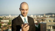 CLOSE UP: Young businessman standing on rooftop texting messages on smartphone video
